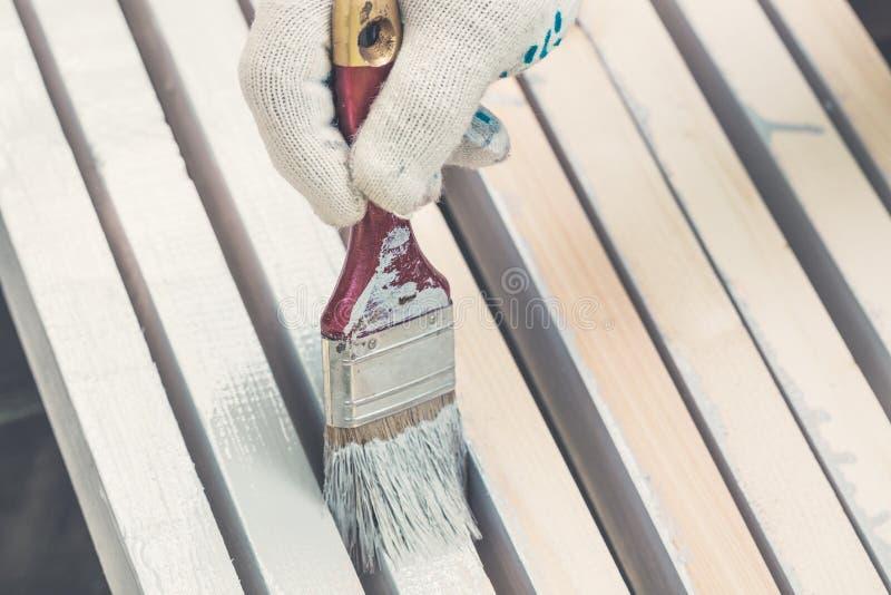 Ręka w rękawiczkach trzyma muśnięcia i farby szalunku zakończenie up stonowany zdjęcia stock