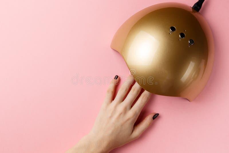 Ręka w ULTRAFIOLETOWEJ lampie zaświeca dla gwoździ na różowym tle obraz stock