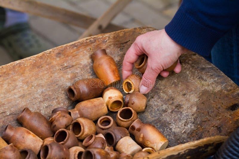 R?ka wybiera dziecko zabawki garnek od stosu mali handmade ceramiczni gliniani dzbanki, puchary i garnki, Ukrai?ska tradycyjna sz fotografia stock