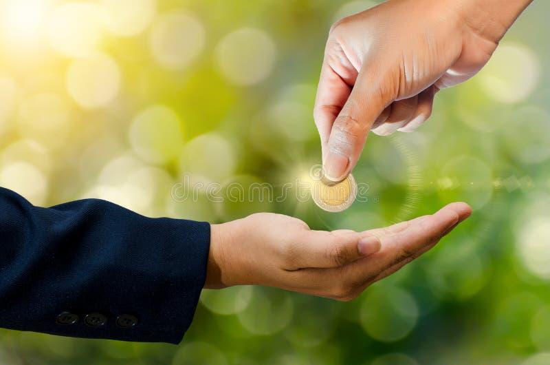 Ręka wysyła monetę zielony bokeh tło daje pieniądze zdjęcia stock