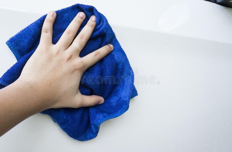 Ręka z błękitnego microfiber cleaning sukiennym samochodem obrazy stock