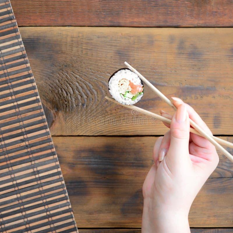 Ręka z chopsticks trzyma suszi rolkę na bambusowym słomianym serwing matowym tle azjatykci jedzenie smażący ryżowi tradycyjni war zdjęcie royalty free