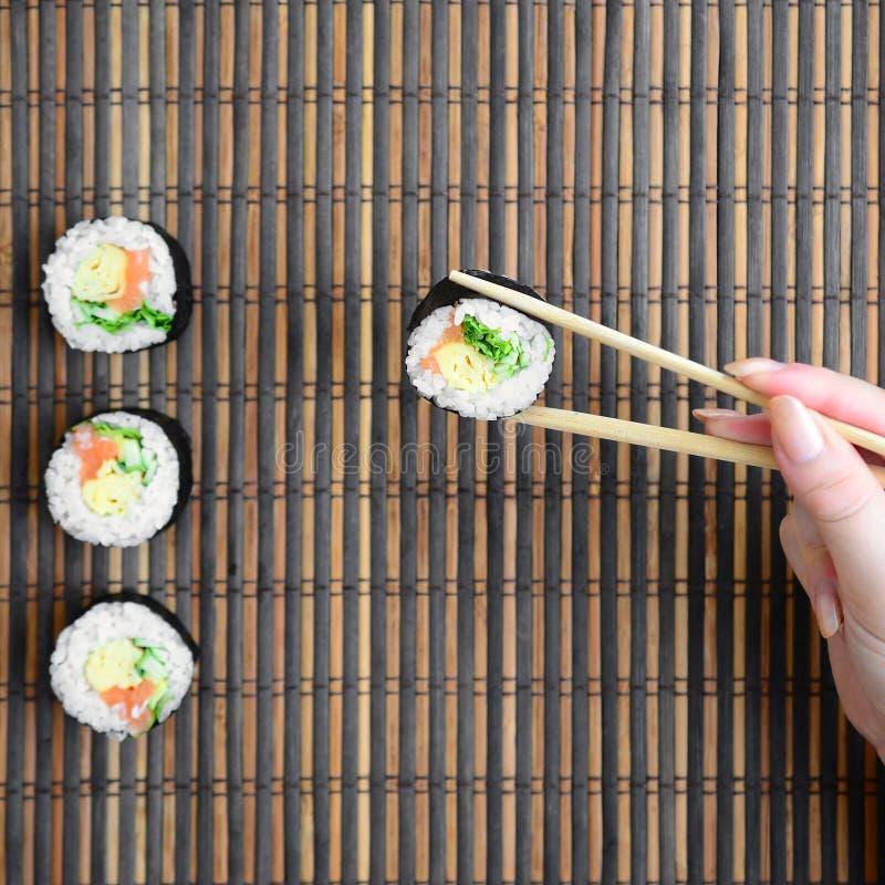 Ręka z chopsticks trzyma suszi rolkę na bambusowym słomianym serwing matowym tle azjatykci jedzenie smażący ryżowi tradycyjni war zdjęcie stock