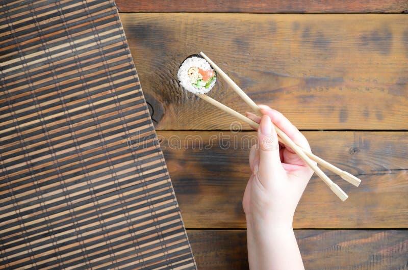 Ręka z chopsticks trzyma suszi rolkę na bambusowym słomianym serwing matowym tle azjatykci jedzenie smażący ryżowi tradycyjni war obraz stock