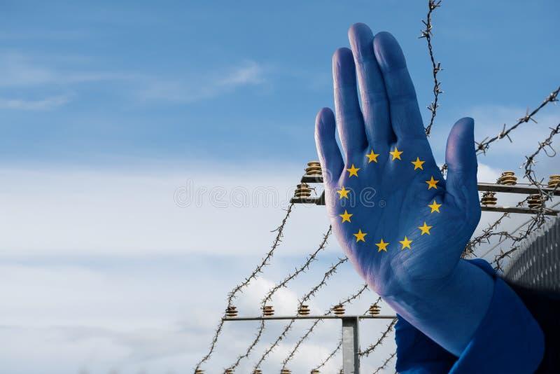 Ręka z Europejski chorągwianym zatrzymuje imigrację uchodźcy, zamazany b obraz royalty free