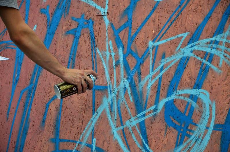 Ręka z kiści puszką która rysuje nowego graffiti na ścianie zdjęcie royalty free