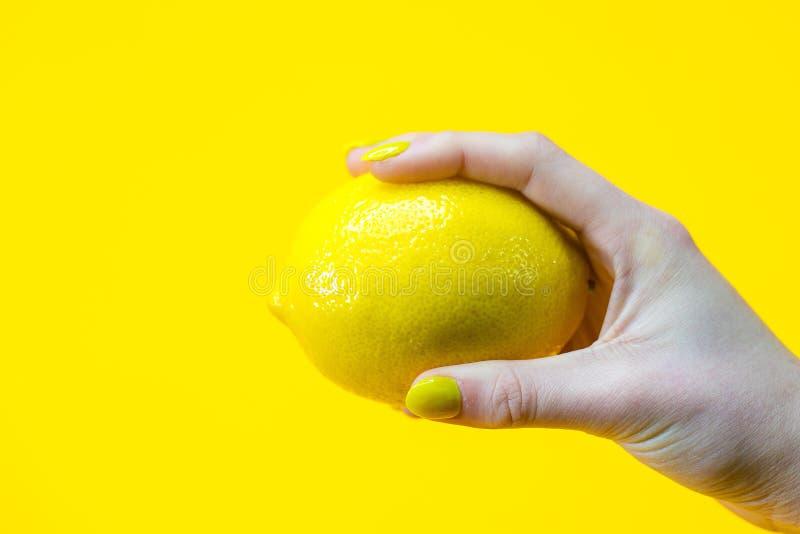 Ręka z kolorem żółtym malującym przybija trzymać świeżą cytrynę obraz stock