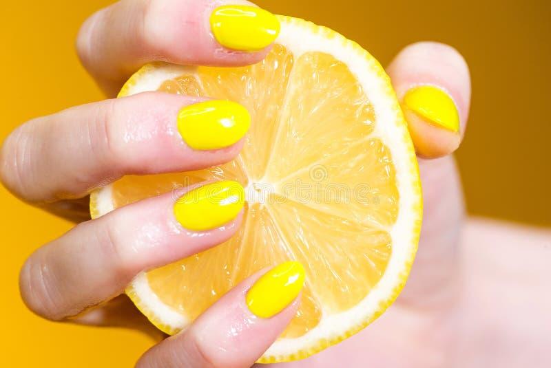 Ręka z kolorem żółtym malującym przybija trzymać świeżą cytrynę obrazy stock