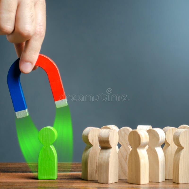 Ręka z magnesem próbuje ciągnąć zieloną postać blisko tłumu ludzie Poborowi nowi pracownicy formacja obrazy stock