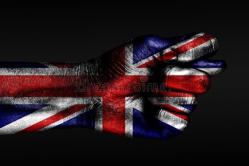Ręka z malującą Wielką Brytania flagą pokazuje figi, znak agresja, nieporozumienie, spór na ciemnym tle obrazy stock