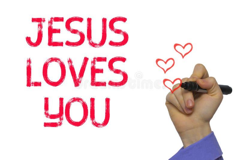 Ręka z markiera writing słowem Jezus Kocha Ciebie zdjęcia stock