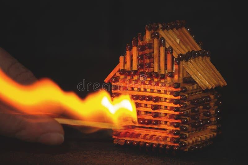 Ręka z płonący zapałczani sety podpala domowy model dopasowania, ryzyko, majątkowego ubezpieczenia ochrona lub zapłon opałowy, fotografia royalty free