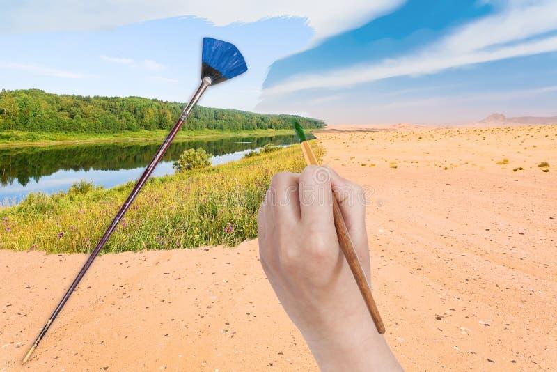Ręka z paintbrush maluje rzekę w piasek pustyni fotografia royalty free