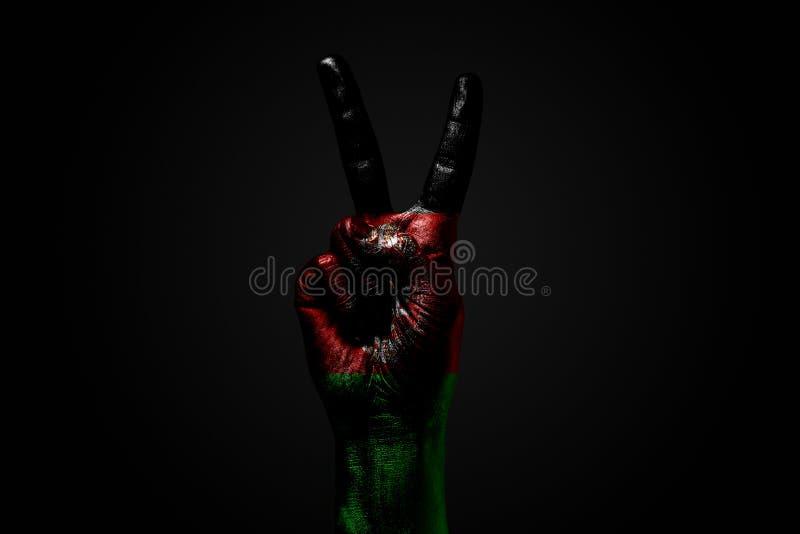 Ręka z patroszoną Afganistan flagą pokazuje pokoju znaka, symbol pokój, przyjaźń, powitania i peacefulness na zmroku, obrazy royalty free