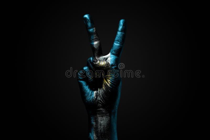 Ręka z patroszoną Argentyna flagą pokazuje pokoju znaka, symbol pokój, przyjaźń, powitania i peacefulness na zmroku, obraz royalty free