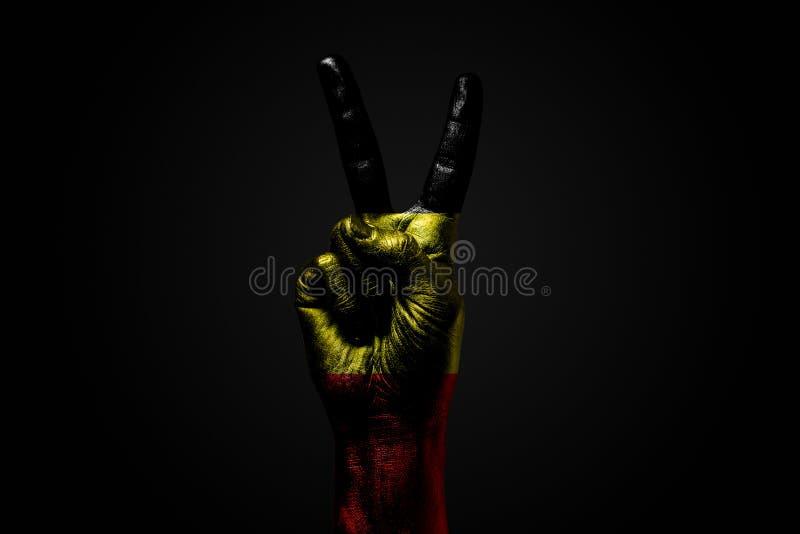 Ręka z patroszoną Belgia flagą pokazuje pokoju znaka, symbol pokój, przyjaźń, powitania i peacefulness na zmroku, fotografia royalty free