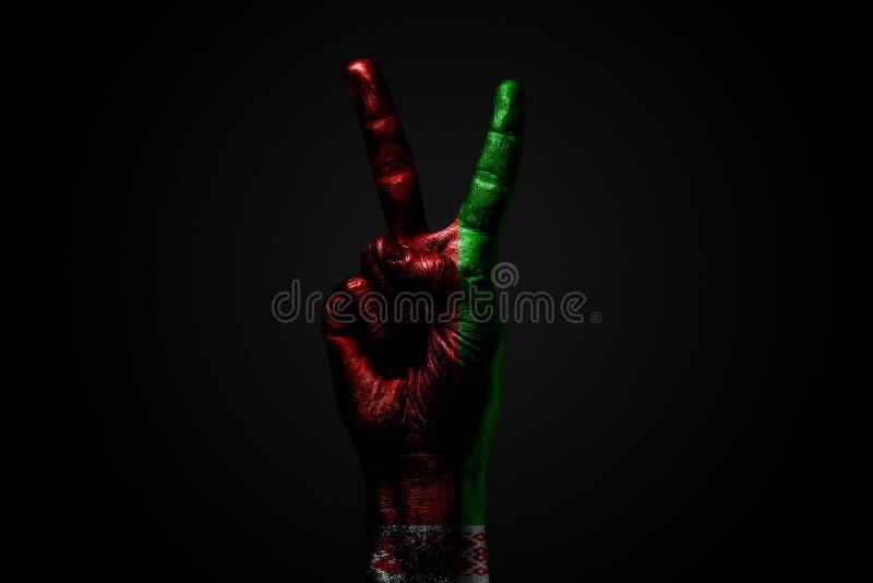 Ręka z patroszoną Białoruś flagą pokazuje pokoju znaka, symbol pokój, przyjaźń, powitania i peacefulness na zmroku, fotografia stock