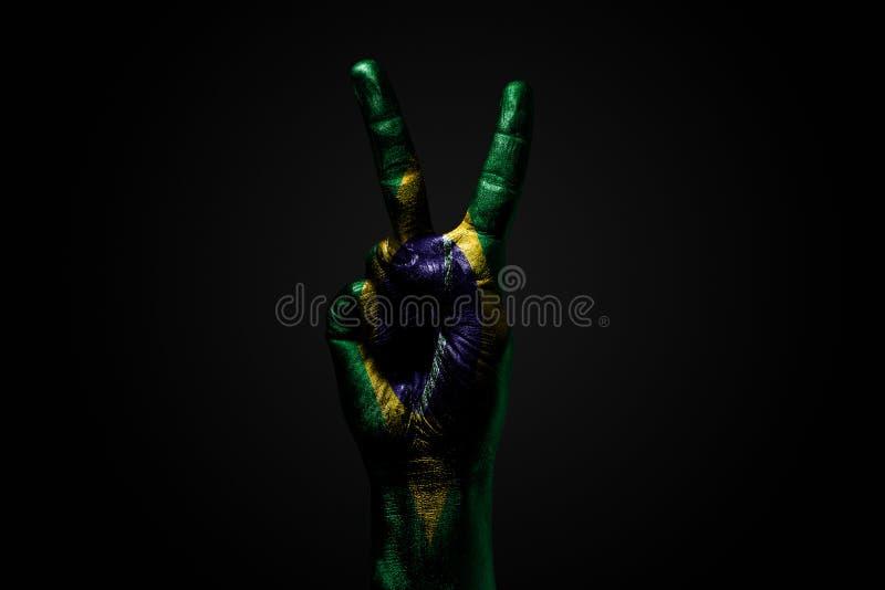 Ręka z patroszoną Brazylia flagą pokazuje pokoju znaka, symbol pokój, przyjaźń, powitania i peacefulness na zmroku, zdjęcie royalty free