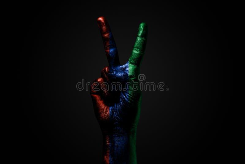 Ręka z patroszoną Dagestan flagą pokazuje pokoju znaka, symbol pokój, przyjaźń, powitania i peacefulness na zmroku, zdjęcia stock
