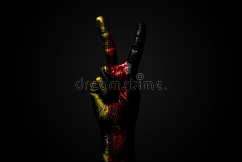 Ręka z patroszoną Niemcy flagą pokazuje pokoju znaka, symbol pokój, przyjaźń, powitania i peacefulness na zmroku, zdjęcia stock