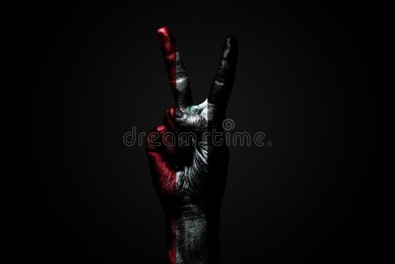 Ręka z patroszoną Syrii flagą pokazuje pokoju znaka, symbol pokój, przyjaźń, powitania i peacefulness na ciemnym tle, obrazy stock