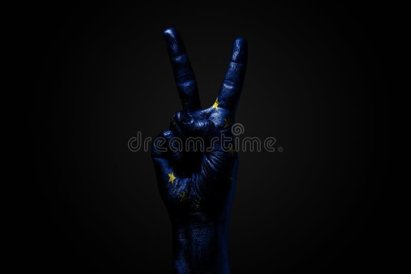 Ręka z patroszoną UE flagą pokazuje pokoju znaka, symbol pokój, przyjaźń, powitania i peacefulness na ciemnym tle, obrazy stock