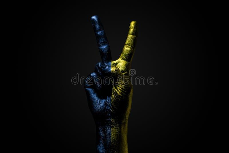 Ręka z patroszoną Ukraina flagą pokazuje pokoju znaka, symbol pokój, przyjaźń, powitania i peacefulness na zmroku, zdjęcie stock