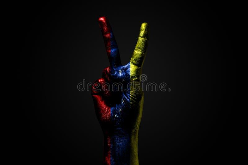 Ręka z patroszoną Wenezuela flagą pokazuje pokoju znaka, symbol pokój, przyjaźń, powitania i peacefulness na zmroku, obraz stock