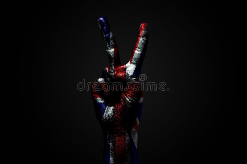 Ręka z patroszoną Wielką Brytania flagą pokazuje pokoju znaka, symbol pokój, przyjaźń, powitania i peacefulness na zmroku, obraz royalty free