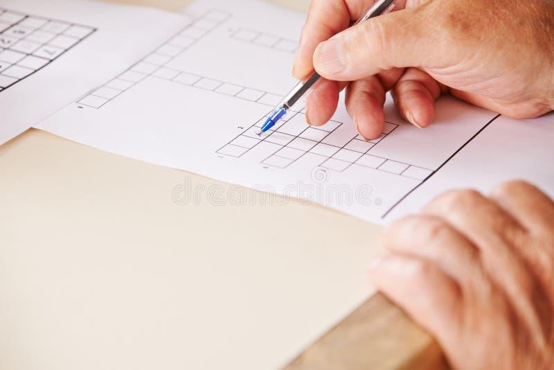 Ręka z piórem rozwiązuje crossword łamigłówkę obrazy royalty free