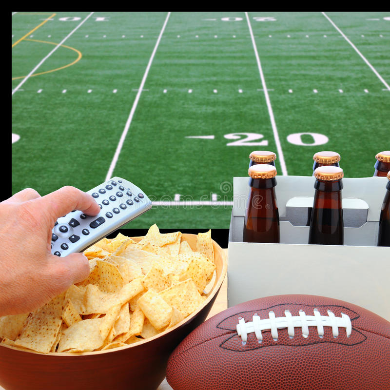 Ręka z pilotem, piwem, układami scalonymi i futbolem TV, obraz royalty free