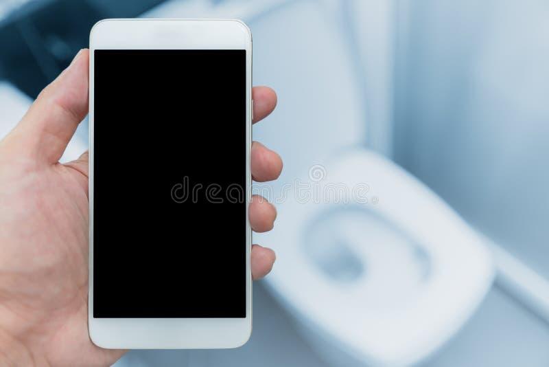 Ręka z smartphone w toaletowym szafy tle obraz stock