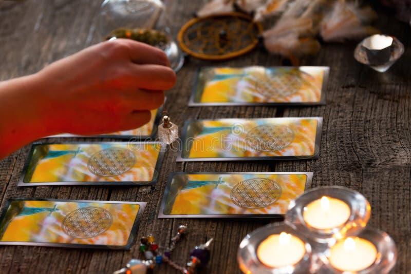 Ręka z wahadłem nad tarot kartami obraz royalty free