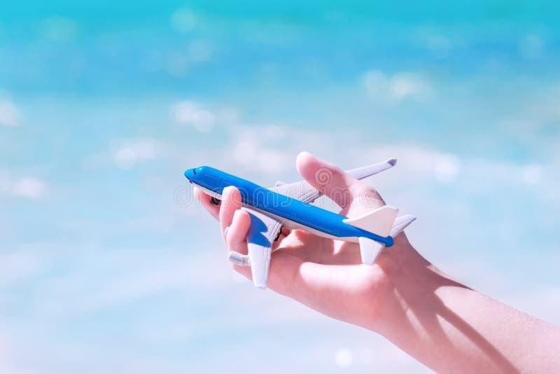 Ręka z zabawkarskim samolotem przeciw błękitne wody i niebu zdjęcia royalty free