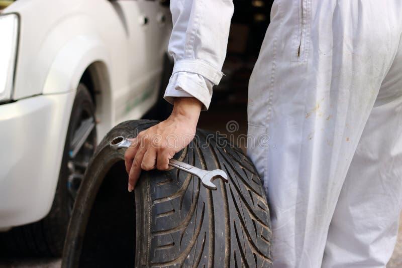 Ręki automobilowy mechanik w mundurze z oponą i wyrwaniem dla załatwiać samochód przy remontowym garażu tłem zdjęcie royalty free