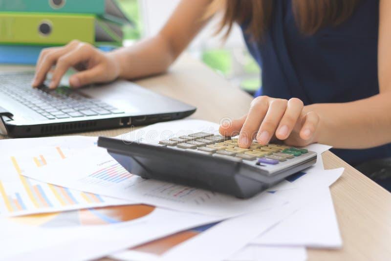 Ręki Azjatycki żeński księgowy pracuje z kalkulatora i komputeru laptopem zdjęcie stock