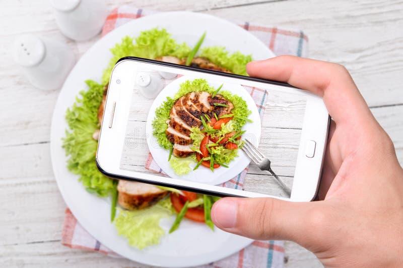 Ręki bierze fotografia kurczaka pierś z smartphone fotografia stock