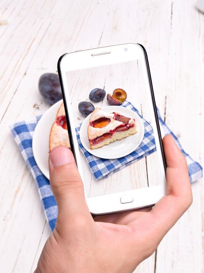 Ręki bierze fotografii śliwki tort z smartphone obrazy stock