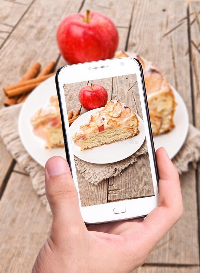 Ręki bierze fotografii jabłczanego tort z smartphone fotografia stock