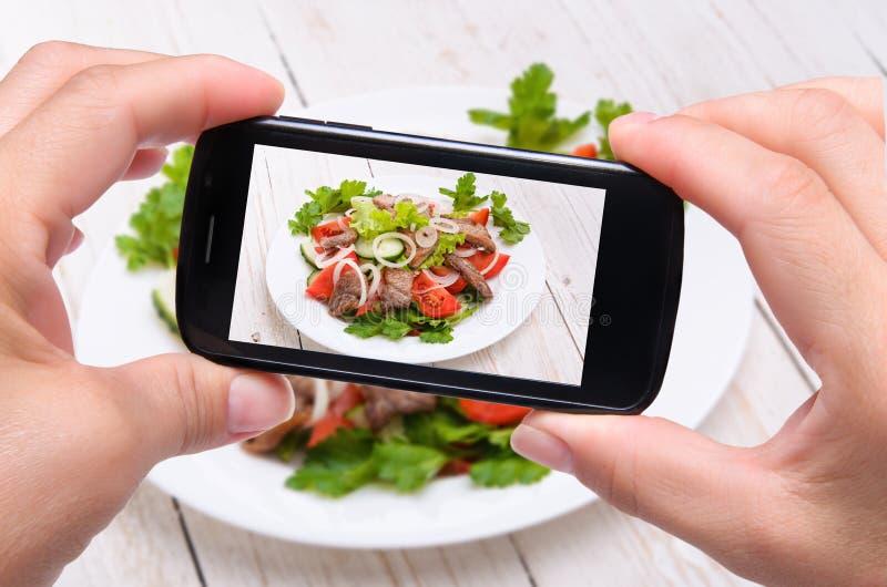Ręki bierze fotografii jarzynowej sałatki z mięsem z smartphone zdjęcie royalty free