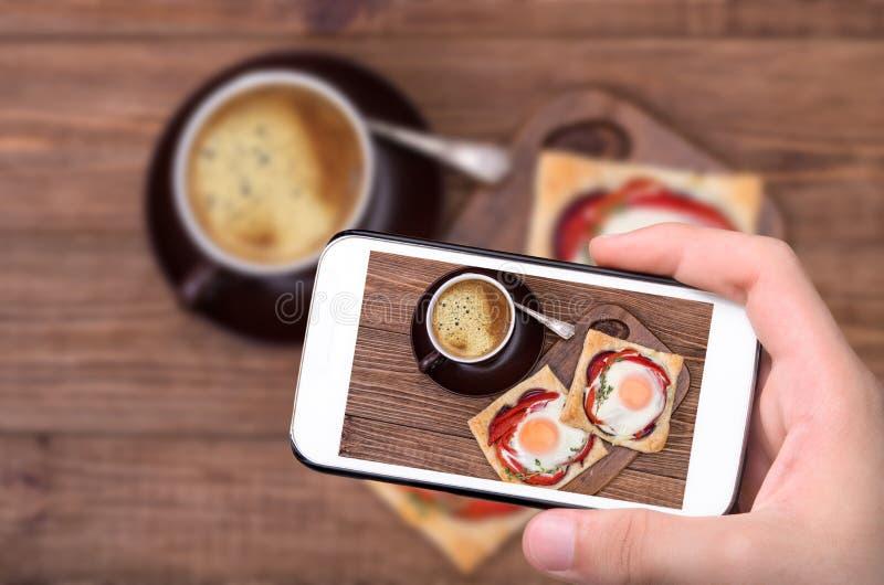 Ręki bierze fotografii surowego wieprzowiny schnitzel z smartphone zdjęcia stock
