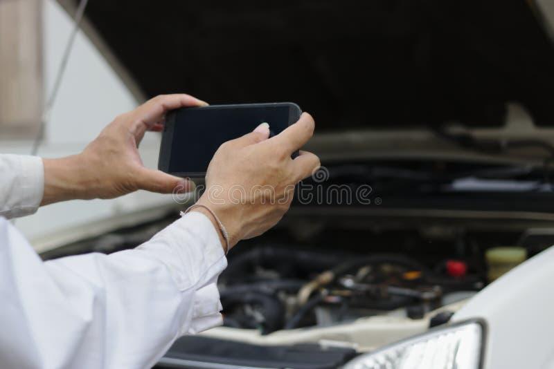 Ręki bierze obrazek z mobilnym mądrze telefonem przeciw samochodowi w otwartym kapiszonie przy remontowym garażem mechanika mężcz zdjęcie royalty free