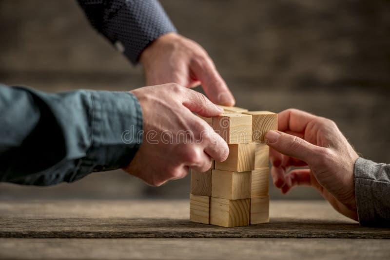 Ręki buduje wierza drewniani bloki zdjęcie stock