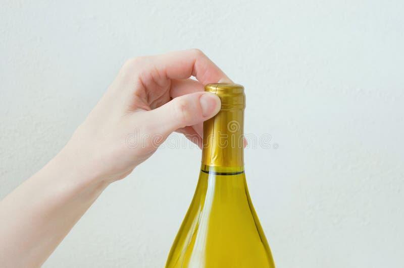 Ręki caucasian dziewczyna otwiera butelkę wino Zako?czenie Bia?y t?o zdjęcie stock