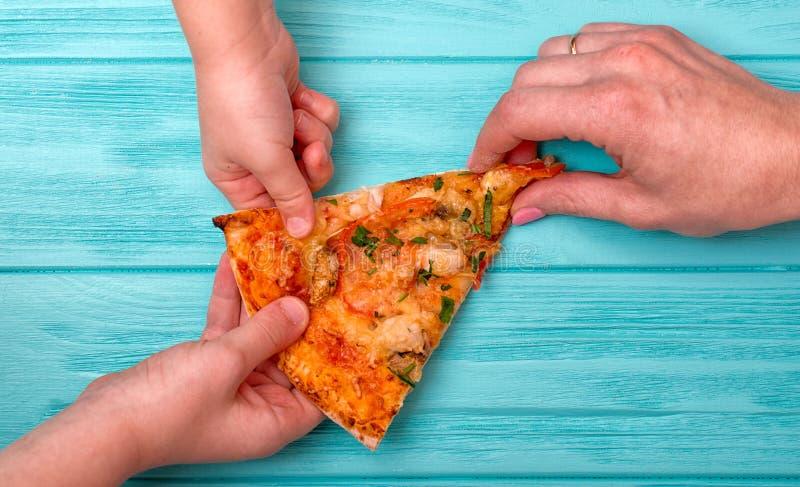 Ręki chcą brać ostatniego kawałek pizza od stołu zdjęcia stock