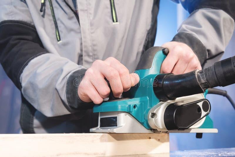 Ręki cieśli woodworking władzy pracujący narzędzia Zamyka w górę pracy elektryczna strugarka obrazy royalty free