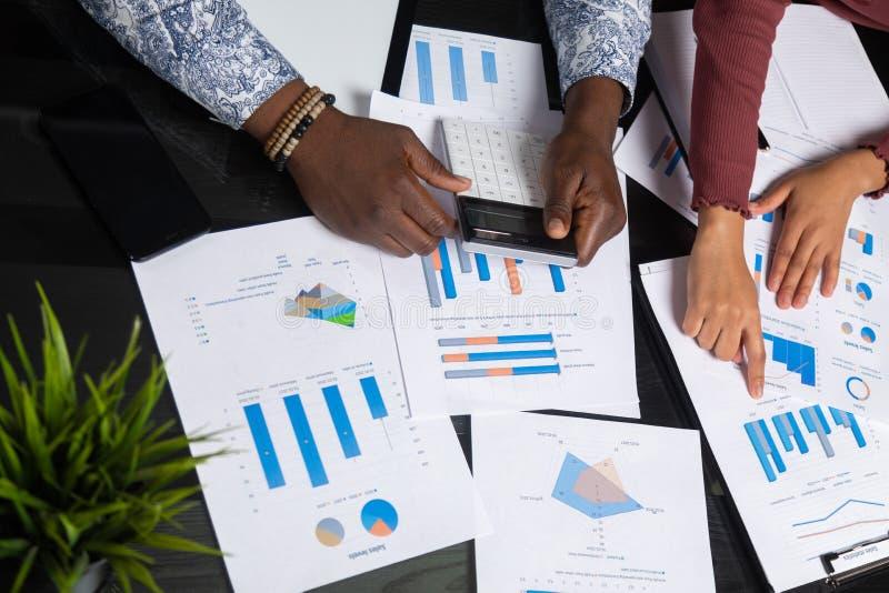 Ręki ciemnoskórzy ludzie chwyta kalkulatora przeciw tłu pieniężni dokumenty w biznes przestrzeni zbliżeniu zdjęcie royalty free