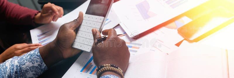 Ręki ciemnoskórzy ludzie chwyta kalkulatora przeciw tłu pieniężni dokumenty w biznes przestrzeni zbliżeniu obraz stock