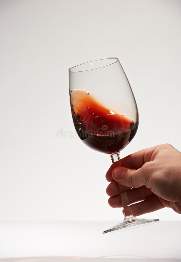 Ręki czerwonego wina potrząsalny szkło zdjęcie royalty free