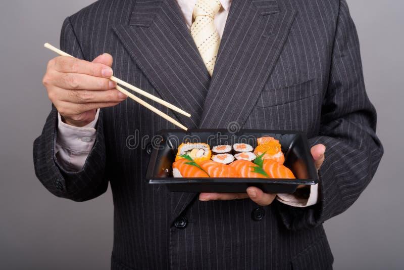 Ręki dojrzałe Azjatyckie biznesmena mienia suszi rolki przeciw gr fotografia royalty free